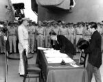 Foreign Minister Mamoru Shigemitsu signs for the Imperial Japanese Government. Standing by is General MacArthur's Chief of Staff, General Richard K. Sutherlin. Note General Richard Sutherlin at left.